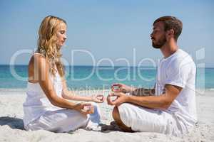 Side view of couple practicing meditation at beach