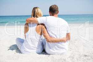Rear view of couple relaxing at beach