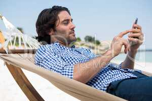 Side view of man using mobile while relaxing in hammock