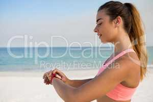Young woman using smart watch while standing at beach