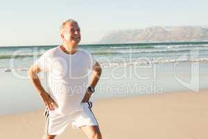 Smiling senior man exercising while standing on sand
