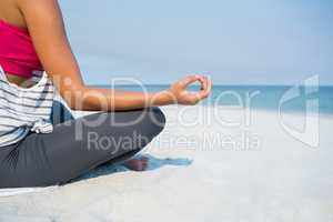 Low section of young woman meditating at beach