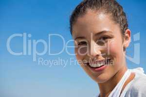 Close up portrait of smiling woman against blue sky