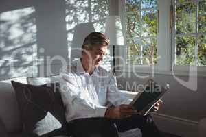 Attentive man reading magazine