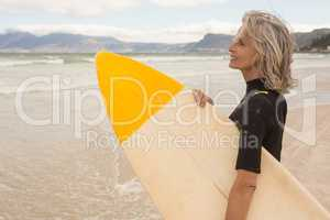 Side view of smiling woman carrying surfboard while standing on shore
