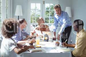 Group of executive using laptop while having breakfast