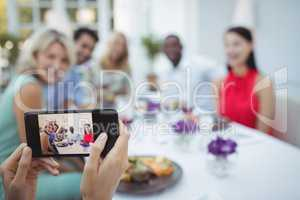 Woman photographing of friends sitting at table