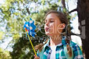 Close-up of girl blowing a pinwheel