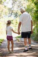 Grandfather and granddaughter holding hands while walking together