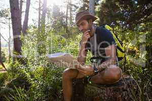 Man reading the map while resting on the tree stump