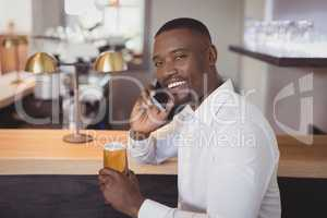 Man talking on mobile phone while having beer