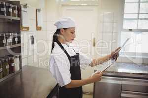 Female chef looking at clipboard in the commercial kitchen