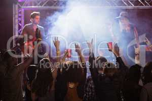 Fans with arms raised enjoying music concert