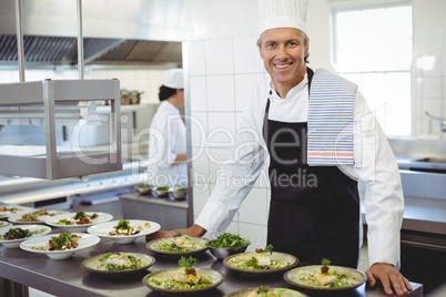 Portrait of happy chef with appetizer plates at order station