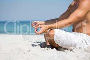 Low section of shirtless man meditating at beach