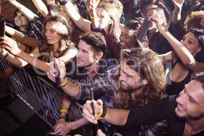 Cheerful crowd photographing music festival