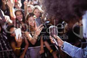 Fans photographing singer performing at nightclub