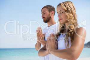 Couple with eyes closed exercising at beach