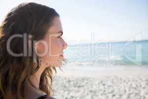 Thoughtful woman looking away at beach