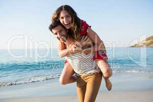Portrait of young man piggybacking his cheerful girlfriend at beach