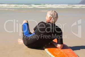 Rear view of senior man in wetsuit sitting by surfboard