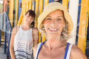 Portrait of happy mother and daughter standing against wall