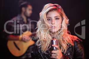 Portrait of female singer holding mic at nightclub