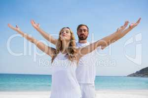 Couple with arms outstretched exercising at beach