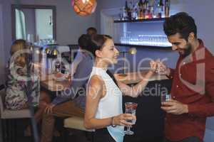 Couple holding glass of drink while dancing in bar restaurant