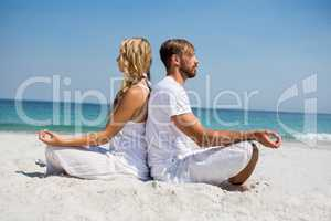 Side view of couple meditating at beach