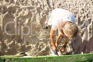 High angle view of senior man tying shoelace while standing on sand