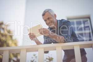 Mature man using digital tablet in balcony