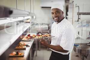 Chef holding dessert tray in commercial kitchen