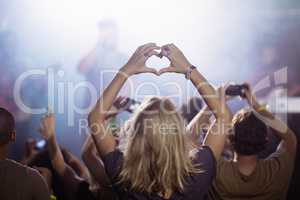 Rear view of woman making heart shape while enjoying at nightclub
