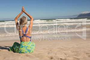 Rear view of woman with arms raised practising yoga while sitting on shore