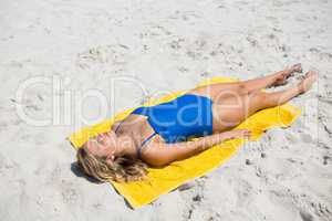 High angle view of woman sunbathing on sand at beach