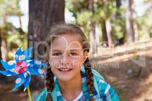 Smiling girl holding a pinwheel in the forest