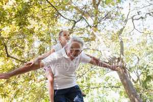 Grandfather giving granddaughter piggy back in the forest