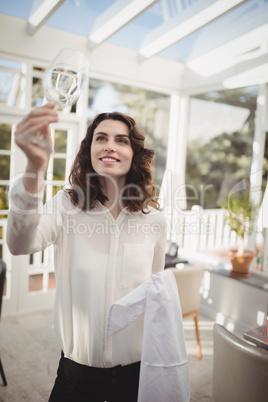 Beautiful waitress cleaning wine glass with napkin