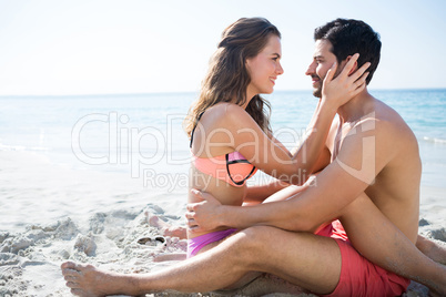 Side view of young couple sitting face to face on sand at beach