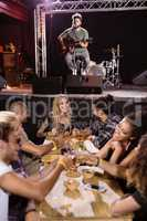 Male musician singing with fans sitting at table