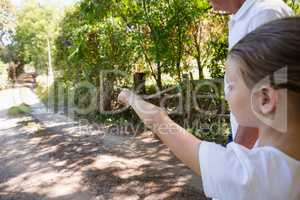Girl with her grandfather pointing at a distance in the forest