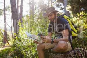 Man using mobile phone while holding the map