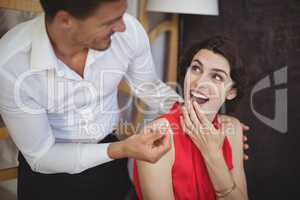 Man offering engagement ring to surprised woman