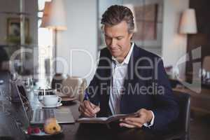 Smiling businessman writing on diary