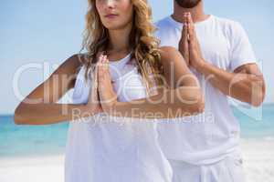 Midsection of couple in praying position exercising at beach
