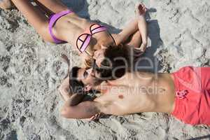 Overhead view of young couple lying together on sand at beach