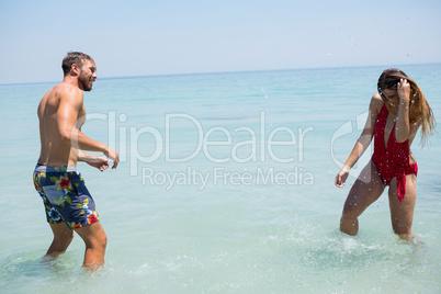 Playful couple enjoying in sea