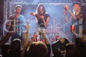 Female singer with musicians performing at nightclub