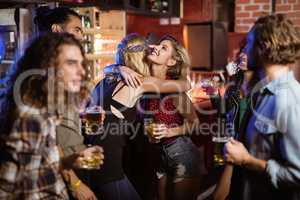 Female friends embracing at club